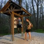 woman looking at park trail sign made out of recycled plastic lumber