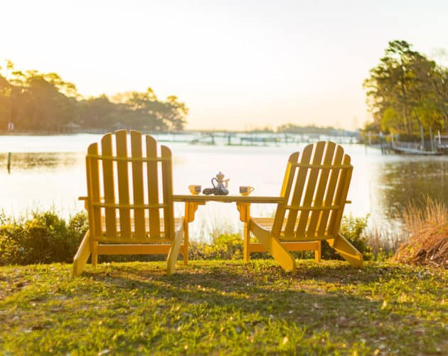 Two yellow plastic Adirondack chairs looking towards a lake