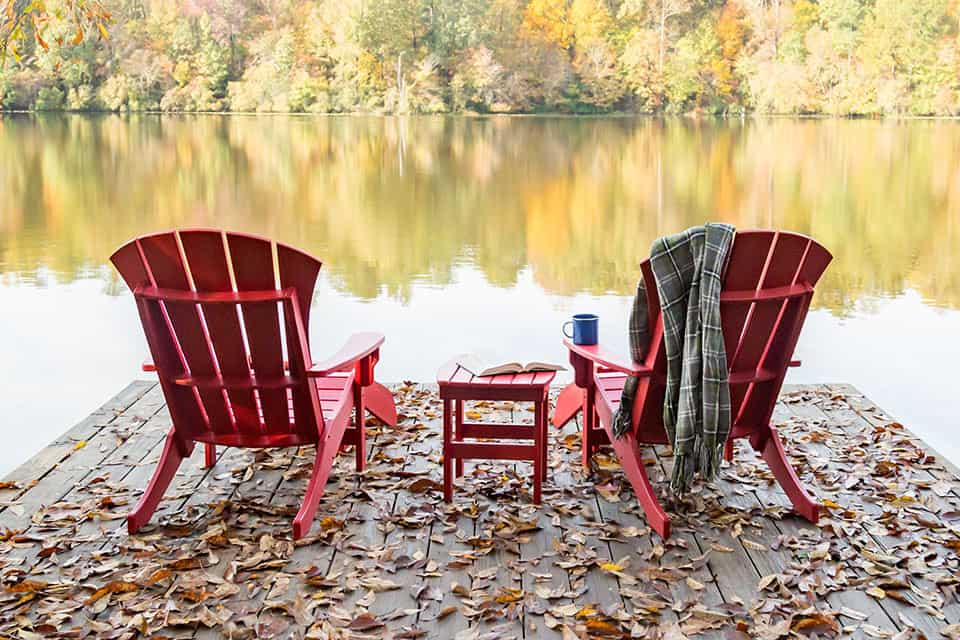 two plastic patio chairs on dock looking towards lake