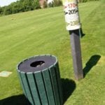 Recycled plastic post and trash can on golf course