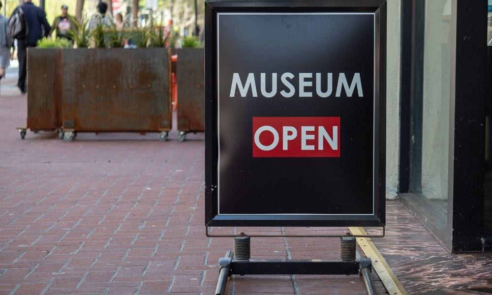"A sign just outside a museum that reads ""Museum Open""."